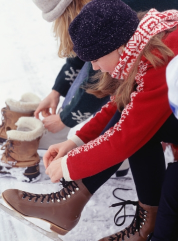 Young girl lacing up figure skates